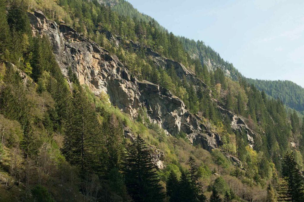 Das Bild zeigt den Schleierwasserfall im Maltatal. In mitten einem Wald steht eine steile, braune Felswand. im linken Bereich stürzt einer der schönsten Vertreter, wenn es um das Thema Wasserfall Maltatal geht.