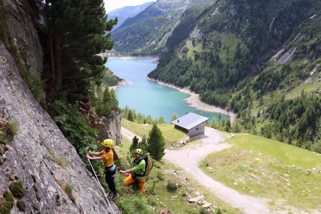 das Bild zeigt passend zum Thema Tipps für Klettersteige mit Kindern einen einfachen Klettersteig mit Vater und kleinem Sohn, in der Kletterarena Damm High im Maltatal, im Hintergrund alpine Landschaft und ein Stausee